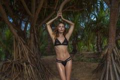佩带黑游泳衣的美丽的白肤金发的魅力妇女摆在棕榈树之间的一个美好的夏日 免版税库存照片