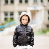 佩带黑皮革起重器的可爱的矮小的都市男孩画象  库存照片