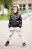 佩带黑皮革起重器的可爱的矮小的都市男孩画象  免版税图库摄影