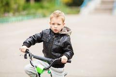 佩带黑皮革起重器的可爱的矮小的都市男孩画象  免版税库存照片