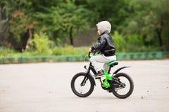 佩带黑皮革起重器的可爱的矮小的都市男孩画象  库存图片