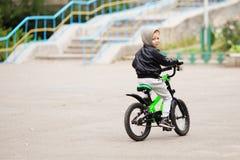 佩带黑皮革起重器的可爱的矮小的都市男孩画象  免版税库存图片