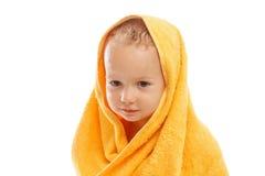 佩带黄色毛巾的愉快的婴孩坐在浴或阵雨以后 免版税库存照片