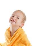 佩带黄色毛巾的愉快的婴孩坐在浴或阵雨以后 免版税库存图片