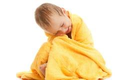 佩带黄色毛巾的愉快的婴孩坐在浴或阵雨以后 库存图片