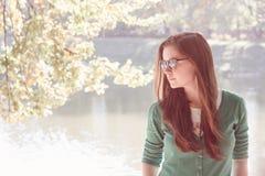 佩带绿色毛线衣和太阳镜的美丽的少妇 库存图片