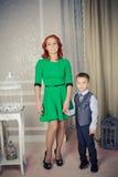 佩带绿色礼服和儿子的红色朝向的母亲 图库摄影
