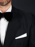 佩带黑衣服和蝶形领结的有胡子的人站立反对黑暗 免版税库存图片