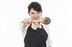 佩带黑围裙的年轻美丽的女性厨师 免版税库存图片