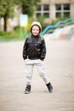 佩带黑leathe的可爱的小男孩全长画象  库存照片