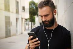 佩带黑T恤杉空白突然反弹盖帽夏时的有胡子的肌肉人 使用智能手机耳机看的年轻人 免版税库存图片