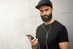 佩带黑T恤杉空白突然反弹盖帽夏时的有胡子的肌肉人 微笑在空的灰色混凝土对面的年轻人 免版税库存图片