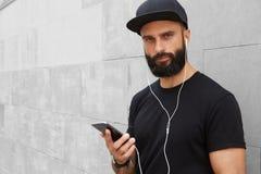 佩带黑T恤杉空白突然反弹盖帽夏时的有胡子的肌肉人 微笑在空的灰色混凝土对面的年轻人 库存图片