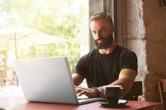 佩带黑T恤杉运作的膝上型计算机木表都市咖啡馆的英俊的有胡子的商人 年轻经理工作笔记本 免版税库存照片