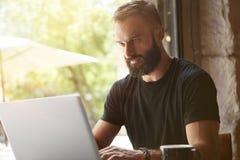 佩带黑T恤杉运作的膝上型计算机木表都市咖啡馆的被集中的有胡子的人 现代年轻经理工作的笔记本 库存照片