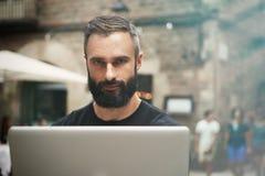 佩带黑T恤杉运作的膝上型计算机都市咖啡馆的特写镜头画象英俊的有胡子的商人 年轻经理工作笔记本 免版税库存图片