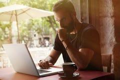 佩带黑T恤杉运作的膝上型计算机都市咖啡馆的被集中的年轻有胡子的商人 人坐的表杯咖啡 免版税库存照片