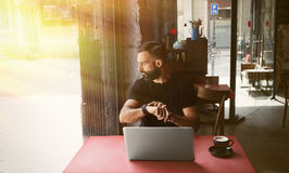佩带黑T恤杉运作的膝上型计算机都市咖啡馆的年轻有胡子的商人 人坐的木表杯咖啡看 免版税库存照片
