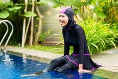 佩带Burkini游泳衣的回教妇女在水池 免版税库存照片