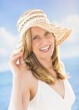佩带Sunhat的可爱的妇女在海滩 免版税库存照片