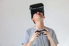 佩带VR凝视和沉浸于的亚裔人在VR赌博 库存照片