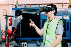 佩带VR凝视的工业工厂劳工接触在工厂里面的虚拟现实世界 免版税库存图片