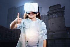佩带VR耳机和显示赞许的快乐的女孩 免版税库存照片
