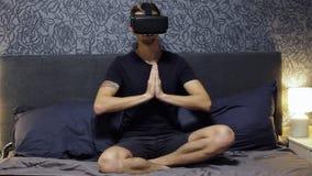 佩带VR耳机的人在卧室 做与虚拟现实玻璃的瑜伽,思考 股票录像