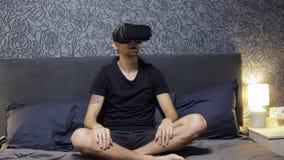 佩带VR耳机的人坐床 查找 手表VR录影 影视素材