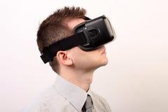 佩带VR虚拟现实Oculus裂口3D耳机,外形的一个人的侧视图看起来正确有一点向上 库存图片