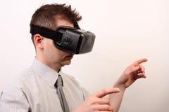 佩带VR虚拟现实Oculus裂口3D耳机,接触或指向某事的一个人的侧视图用他的手 库存图片
