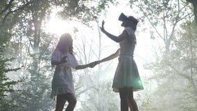 佩带VR风镜的女孩握有她的朋友的手并且通过探索虚拟现实的森林走- 股票录像