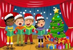 佩带xmas帽子唱歌圣诞颂歌诞生剧阶段的多文化孩子 免版税库存照片