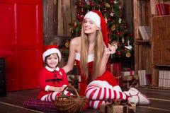 佩带xmas礼服和帽子装饰的两个女孩 免版税库存图片
