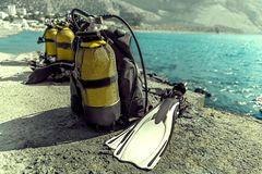 佩戴水肺的潜水谎言的设备在岸 免版税库存照片
