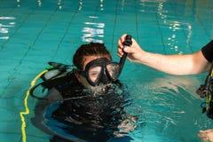 佩戴水肺的潜水路线水池有辅导员的少年女孩 免版税库存图片