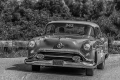 佩萨罗COLLE圣BARTOLO,意大利- 2018年5月17日- :在集会Mille Miglia 2018的OLDSMOBILE超级88 1954老赛车著名i 免版税库存图片
