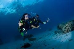 佩戴水肺的潜水学生和辅导员 免版税库存图片