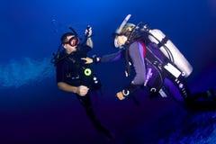 佩戴水肺的潜水辅导员和学生 库存图片