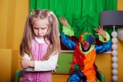 使一个哀伤的女孩振作的小丑尝试 免版税库存图片