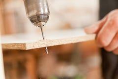 使一个木板不耐烦的钻头 图库摄影