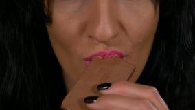 使上瘾对甜点吃一个棕色巧克力糖酒吧慢动作的少妇特写镜头  股票视频