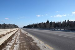 使与有金属的郊区高速公路在边的篱芭和森林环境美化在蓝天下在晴天 免版税库存图片