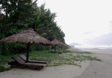 使与木躺椅的海场面靠岸在棕色草秸杆伞小屋下 免版税库存图片