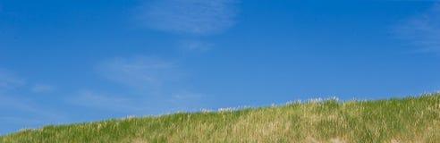 使与沙丘的海岸靠岸在与蓝天的一个晴天 免版税库存照片