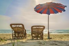 使与沙滩伞的床靠岸在海海滩 库存图片