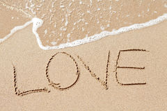 使书面的爱字靠岸 免版税库存图片