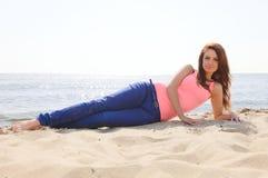 使享用夏天星期日沙子的节假日妇女靠岸看起来愉快 图库摄影