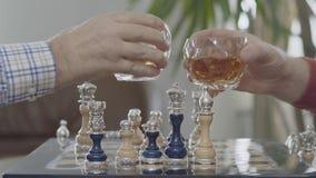 使他们的与whiskeyover的两个人玻璃叮当响棋盘 与站立银色的插入物的美好的国际象棋棋局  股票录像