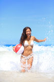 使使用与球的妇女靠岸有乐趣飞溅 免版税图库摄影